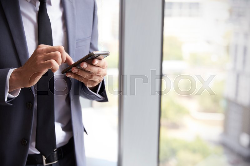 Close Up Of Businessman Checking Messages On Mobile Phone, stock photo