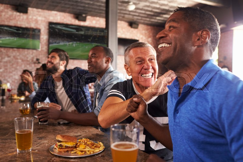 Male Friends In Sports Bar Watch Game And Celebrate, stock photo