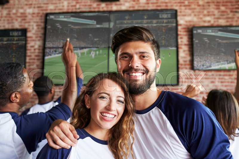 Portrait Of Couple Watching Game In Sports Bar On Screens, stock photo