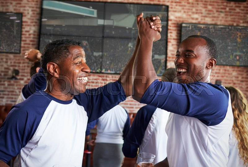 Male Friends Watching Game In Sports Bar Celebrating, stock photo