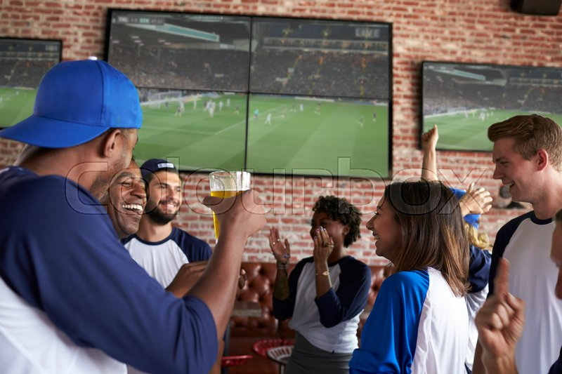Friends Watching Game In Sports Bar On Screens Celebrating, stock photo