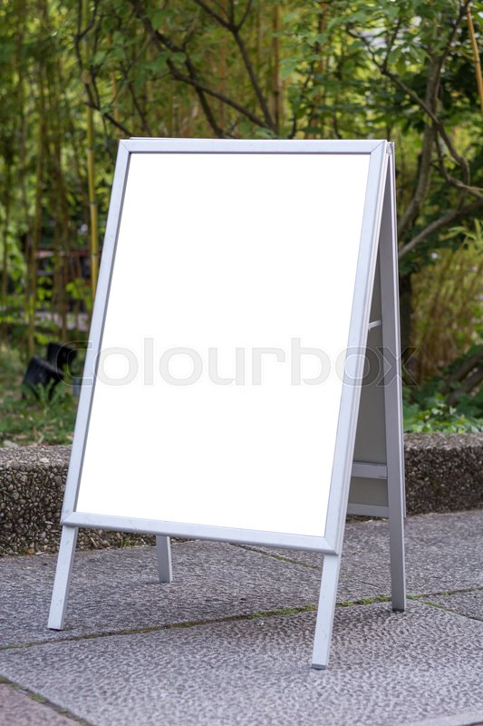 Blank ad space sign infront of trees in a park on the ground, stock photo