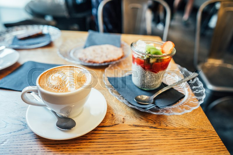 Cappuccino with beautiful foam and spoon in white cup and dessert, stock photo