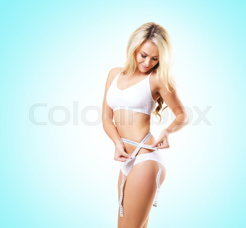 Fit and sporty girl in white underwear. Beautiful and healthy woman measuring her perfect body over cyan background. Sport, fitness, diet, weight loss and healthcare concept, stock photo