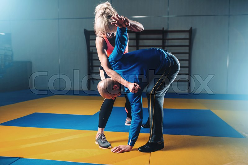 Male and female fighters, self defense technique, self-defense workout with personal trainer in gym, martial art, stock photo