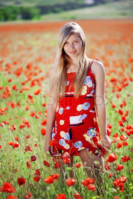 Blond girl in red dress posing at poppy meadow | Stock Photo ...