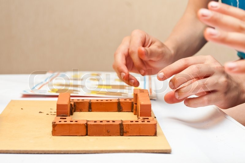 Children Build A Small House Made Of Bricks Stock Photo