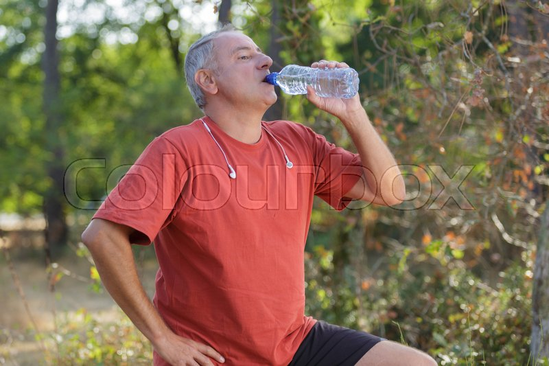 Middle aged man drinking water from bottle, stock photo