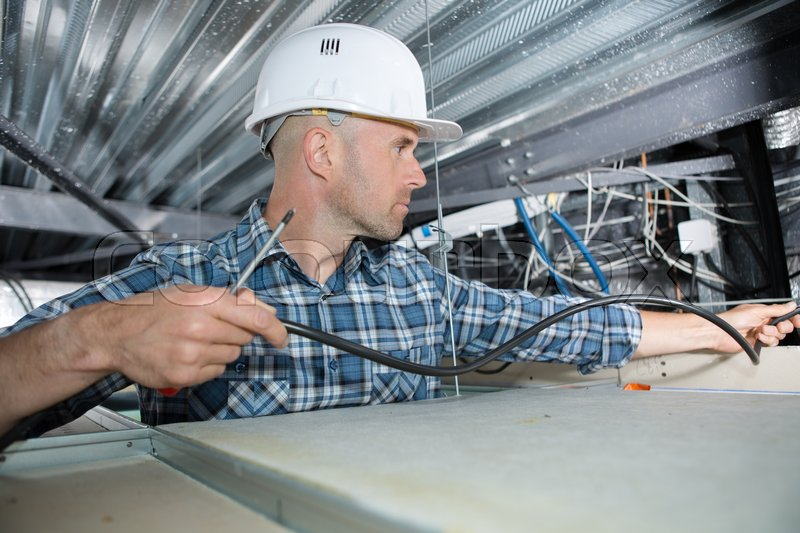 Electrician installing cable in roof space, stock photo