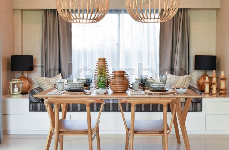 Dining wooden table and comfortable chairs in modern home with elegant table setting, stock photo