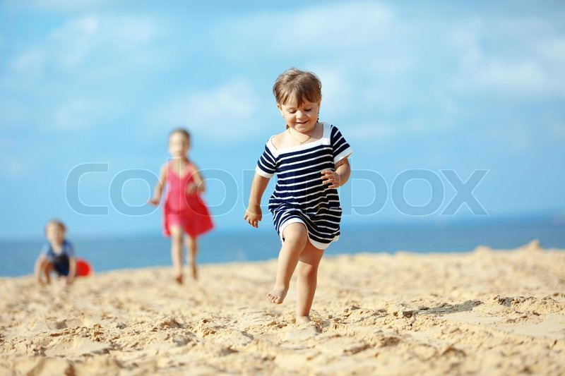 Kids Playing Running On Sand At The Beach Stock Photo
