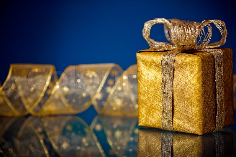 Gold christmas gift box and ribbon on dark blue background for Blue and gold christmas
