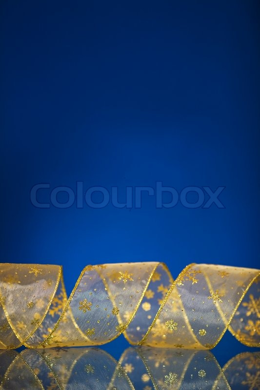 Stock image of 'Christmas border from gold ribbon on dark blue ...