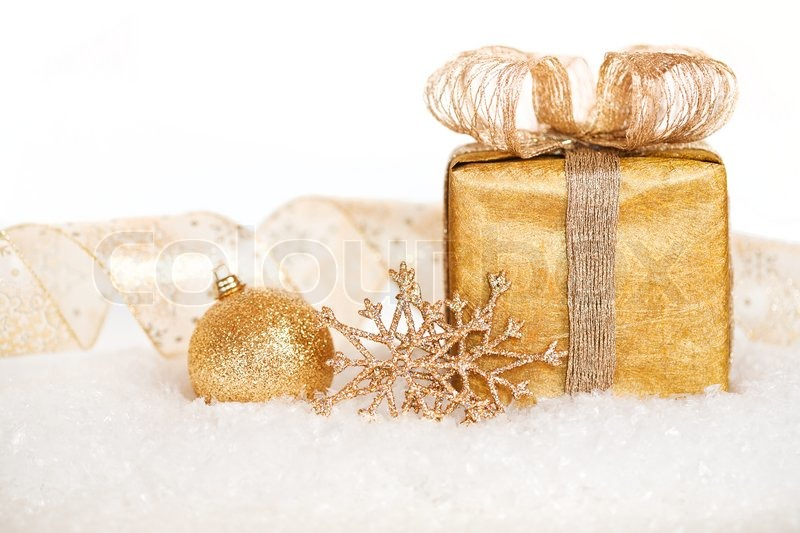 Gift Box And Gold Decorations In Snow On White Background