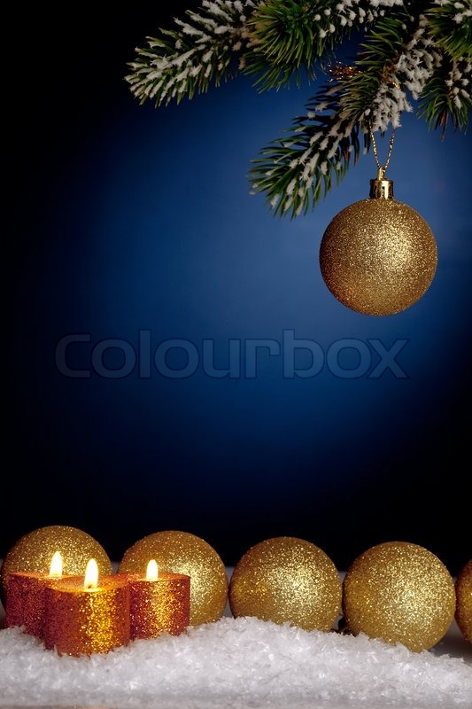 gold christmas tree decorations and candles in snow on blue and gold christmas