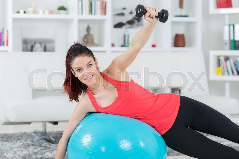 Young woman training at home staying fit, stock photo