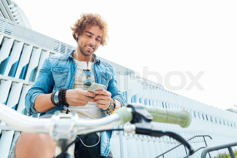Handsome young man listening music with mobile phone and fixed gear bicycle in the street, stock photo