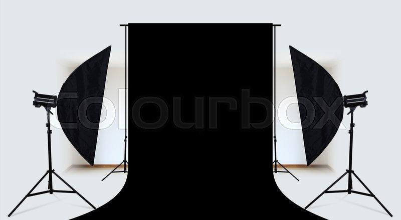 Photo studio with lighting equipment and black backdrop, stock photo