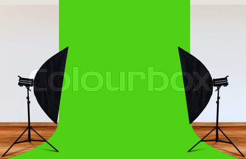 Photo studio with lighting equipment and green backdrop, stock photo