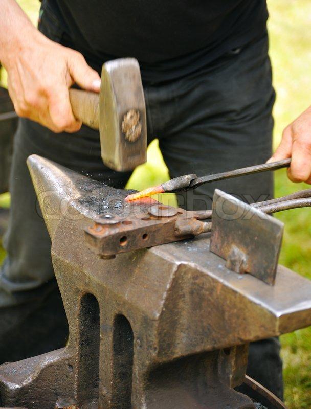 Blacksmith Hammering Hot Iron On Anvil Stock Photo