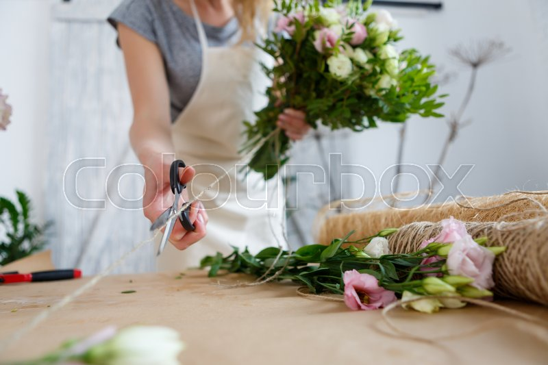 Girl florist makes beautiful bouquet of white and pink flowers, stock photo