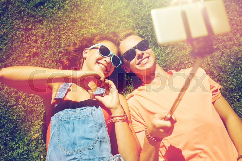 Love and people concept - happy teenage couple in sunglasses lying on grass and taking selfie on smartphone at summer, stock photo