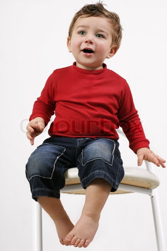 Adorable happy young toddler child sitting on a white for Toddler sitting chair