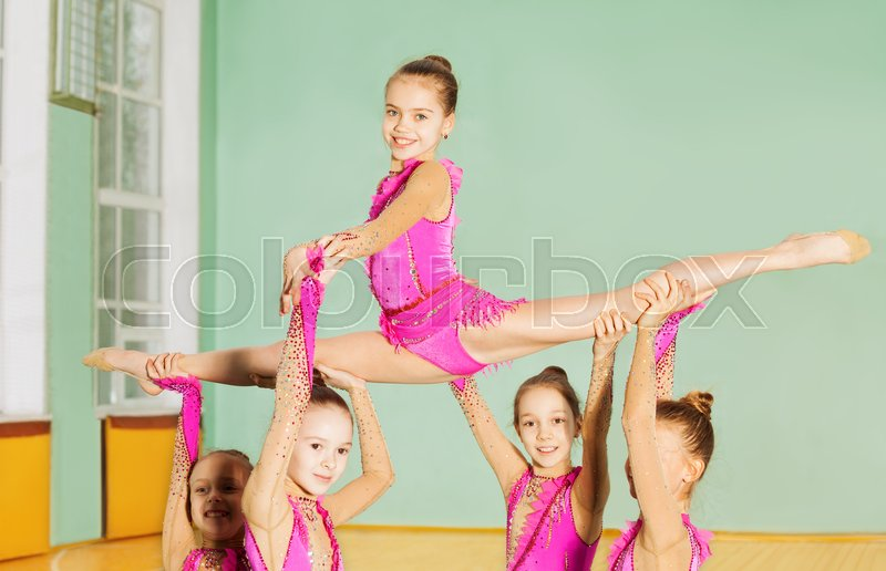 Group of beautiful preteen girls performing rhythmic gymnastics element in sports hall, stock photo