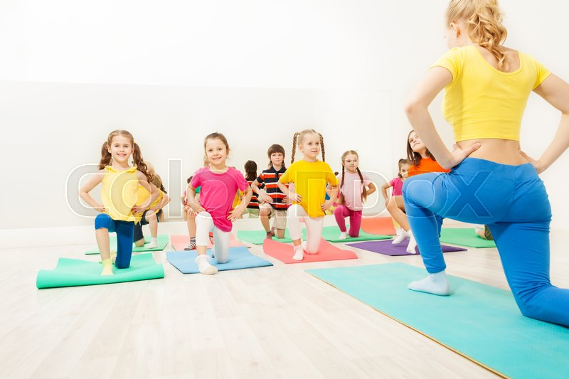 Group of happy kids doing exercises in gym with female gymnastics coach, stock photo