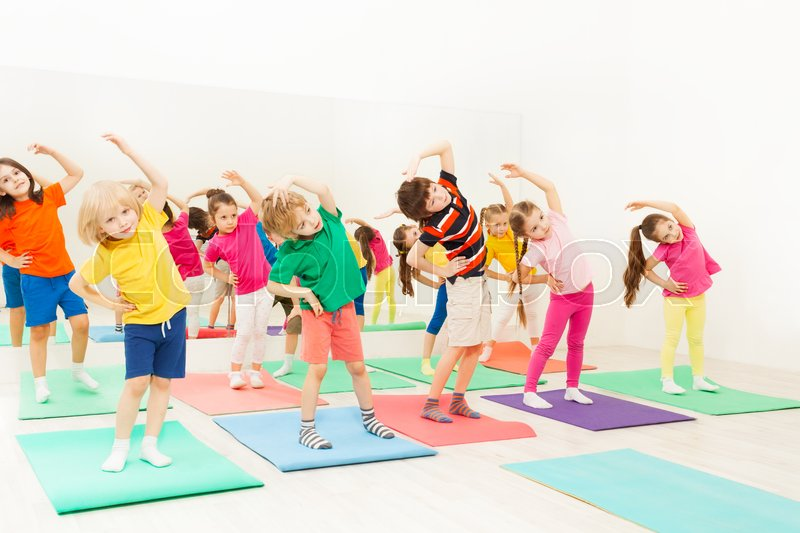 Group of happy kids, 5-6 years old girls and boys, doing side bending exercises in gym, stock photo