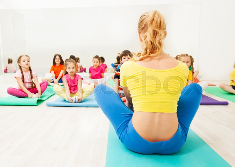 Back view of female gymnastic coach and kid\'s group doing butterfly stretch on yoga mats in exercise room, stock photo
