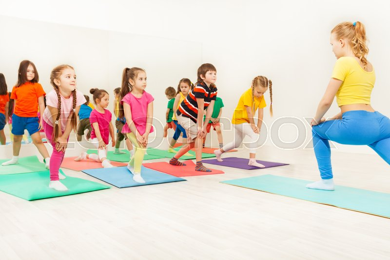 Group of happy six years old kids and female instructor doing gymnastic exercises in fitness class, stock photo