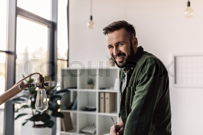 Bearded businessman in casual clothing smiling at camera in modern office, stock photo