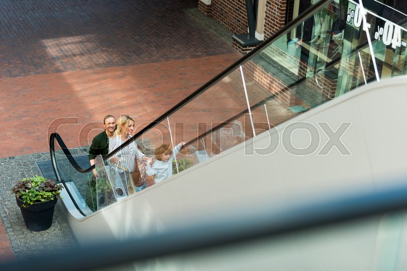 High angle view of happy parents with cute little son standing on escalator in shopping mall, stock photo