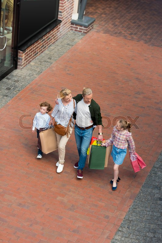High angle view of happy family with two children holding paper bags and walking together, stock photo