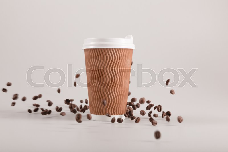 Disposable coffee cup with falling coffee grains isolated on beige, stock photo