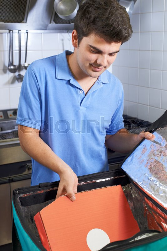 Pizza Delivery Person Putting Food Into Insulated Bag In Restaurant Kitchen, stock photo