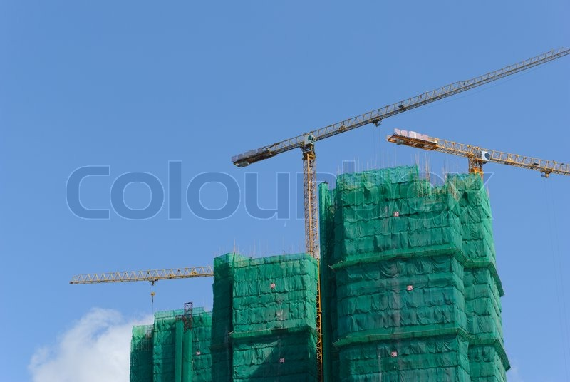 Construction site with crane and building against blue sky, stock photo