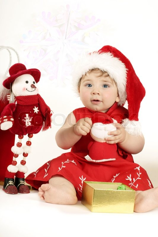 a beautiful nine month old baby girl in a red dress and santa hat playing with christmas presents stock photo colourbox