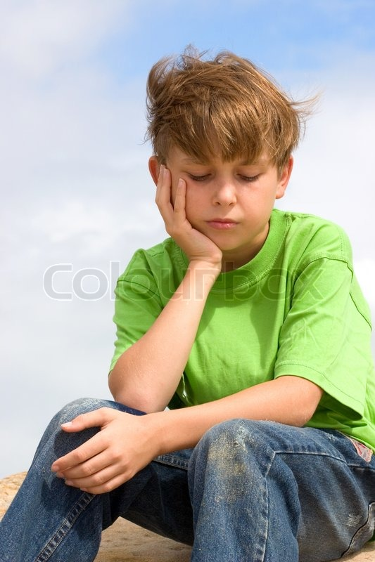 A sad, unhappy, depressed, dejected child sitting alone ...