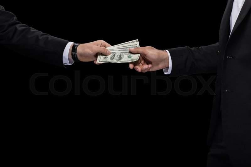 Cropped view of businessman giving money and bribing business partner, isolated on black, stock photo