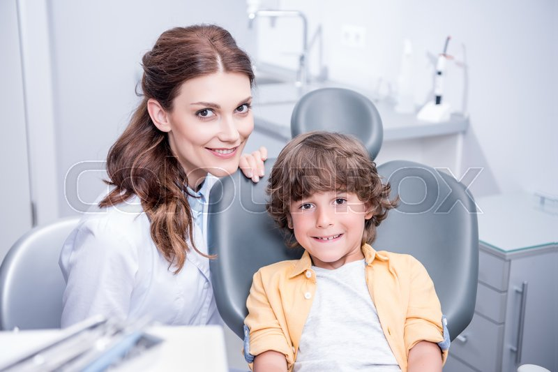 Portrait of professional dentist and little boy in dentist office, stock photo