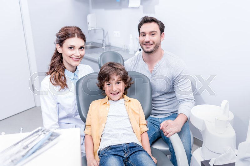 Little smiling boy with father and dentist at dentist office, stock photo