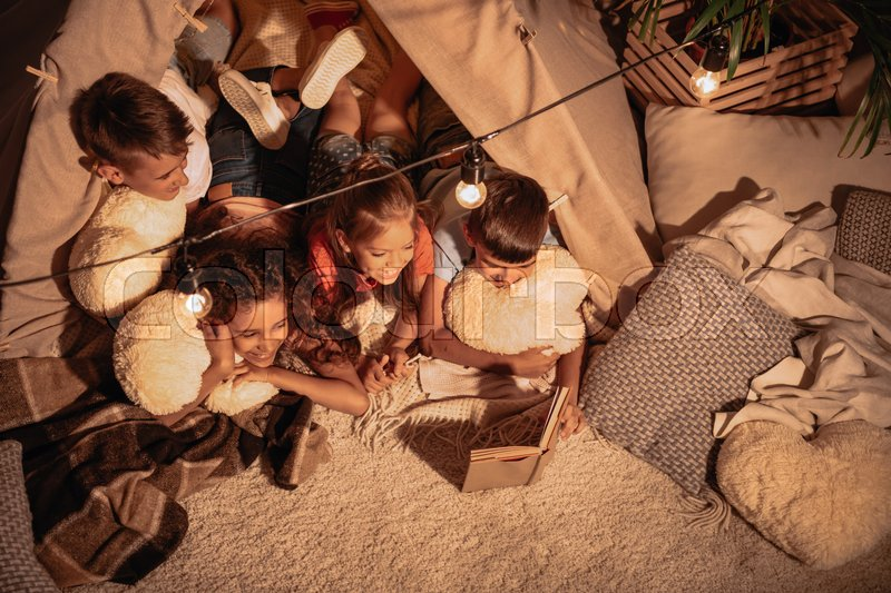 High angle view of multicultural group of children reading book together, stock photo