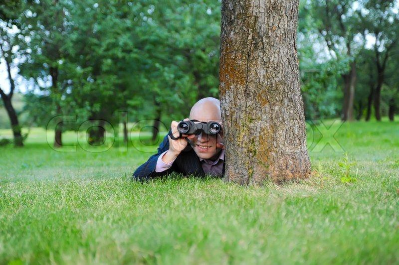 man in the green park looking through binoculars stock