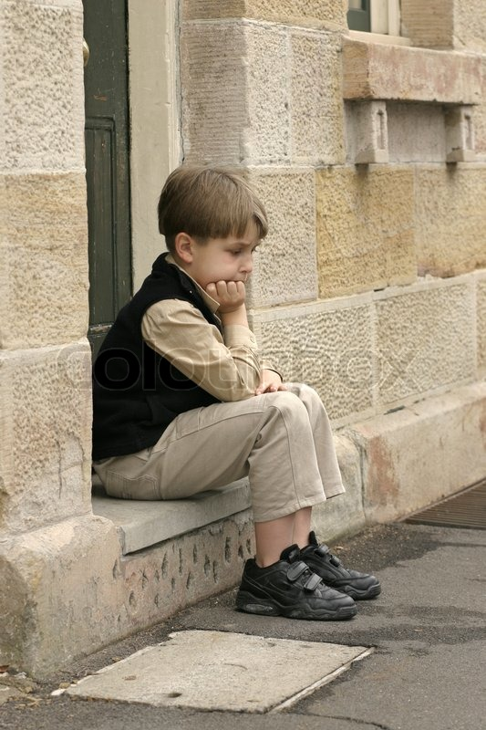 young boy sitting on the doorstep feeling a little glum
