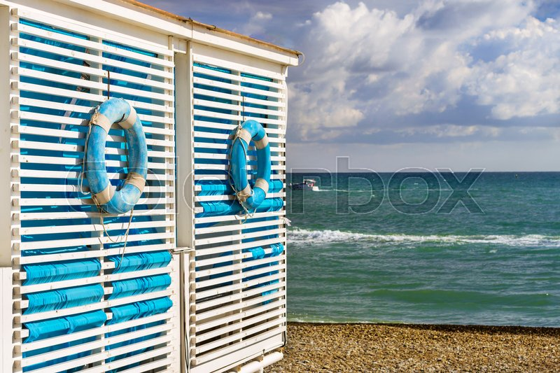 blue lifebuoy hanging on wooden wall beach tent on shore of a pebbly