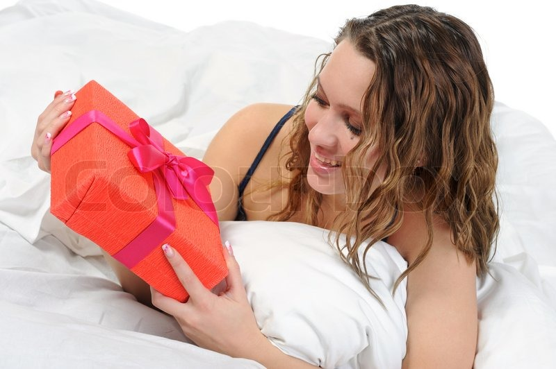 Young woman with a gift box in the bed Isolated on white background, stock photo