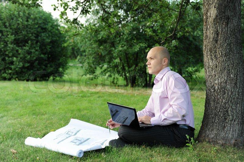 Mann mit laptop sitzen in der n he eines baumes im park for Wildparks in der nahe