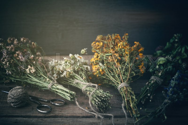 Bunches of healing herbs on wooden board. Herbal medicine. Retro toned photo, stock photo
